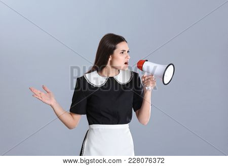 Young chambermaid with megaphone on grey background