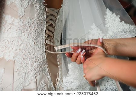 Bridesmaid Hands Lace Up White Wedding Dress On The Back