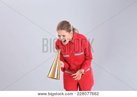 Young female emergency doctor shouting into megaphone on grey background