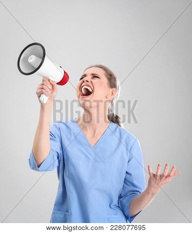 Young female doctor shouting into megaphone on grey background