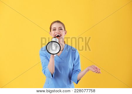 Young female doctor with megaphone on color background