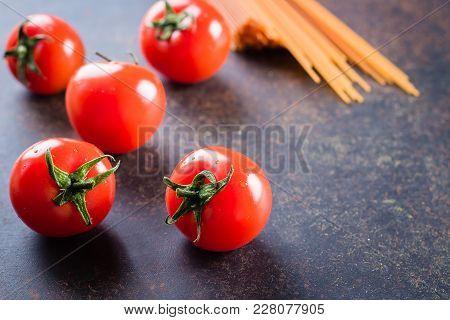 Tomato Pasta Ingredients. Cherry Tomatoes And Spaghetti Pasta On Dark Stone Table Background. Italia