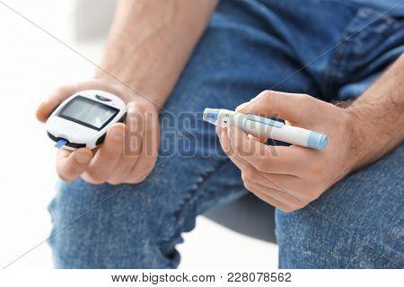 Diabetic man holding digital glucometer and lancet pen, closeup
