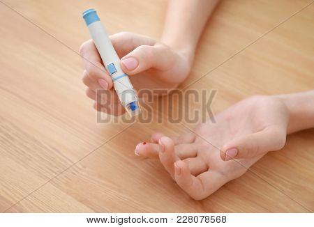 Diabetic woman taking blood sample with lancet pen over table