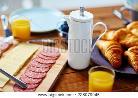 food and hot drinks concept - coffee pot on served wooden table at breakfast