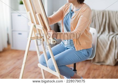 art, creativity and people concept - artist with easel drawing picture at studio