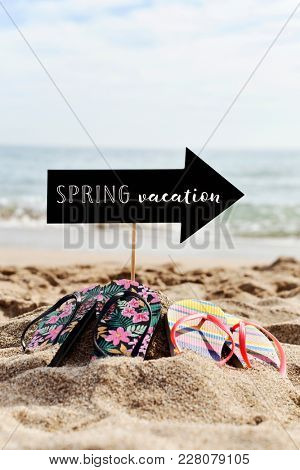 two pairs of colorful flip-flops on the sand of a quiet beach and an arrow-shaped signboard with the text spring vacation written in it, and the sea in the background