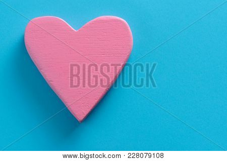 closeup of a pink three-dimensional heart on a blue background, with a blank space on the right