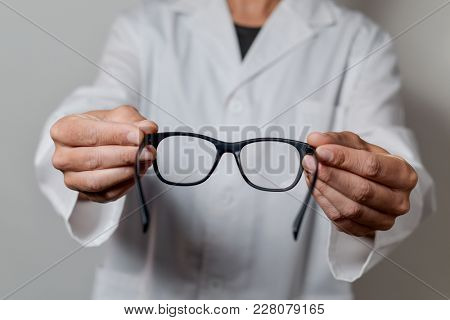 closeup of a young optician man bringing a pair of eyeglasses to the observer