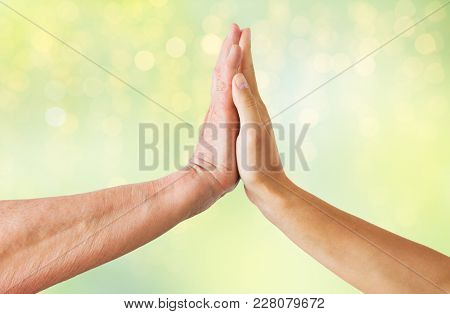 people, age and charity concept - close up of senior and young woman hands touch over green lights background