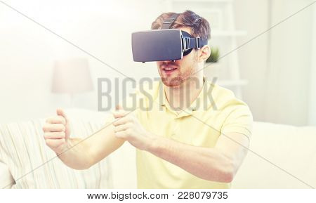 3d technology, virtual reality, gaming, entertainment and people concept - young man with virtual reality headset or 3d glasses  playing racing videogame at home