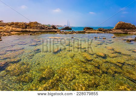 Ruins of the ancient city and port of Caesarea. Flooded in the sea ruins and remains of ancient forts and fortifications. Spring day in Israel. Concept of archeological and historical tourism