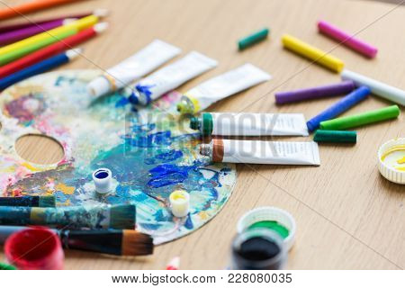 fine art, creativity, painting and artistic tools concept - close up of acrylic color or paint tubes with crayons and palette