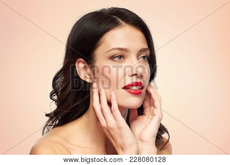 beauty, make up and people concept - happy smiling young woman with red lipstick over beige background touching her face