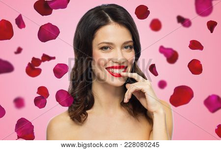 beauty, valentines day, make up and people concept - happy smiling young woman with red lipstick posing over rose petals on background