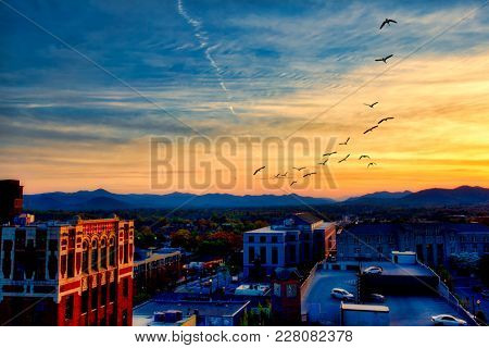 The Blue Ridge Mountains add drama to the skyline of Asheville, North Carolina at sunset.