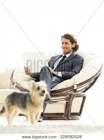 modern businessman with laptop sitting in living room.