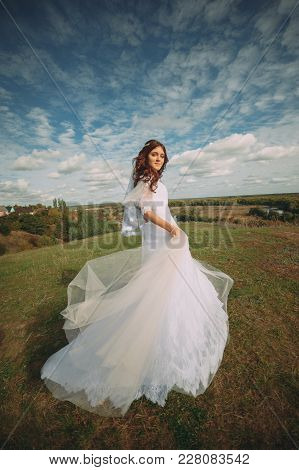 The Bride Is Spinning In The Field. Flying Dress