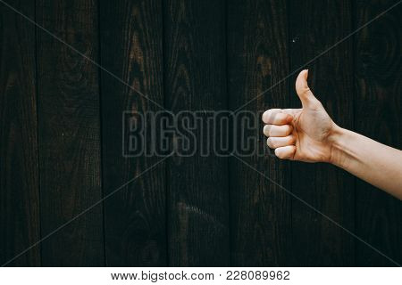Closeup Of Male Hand Showing Thumbs Up Sign Against Wooden Background