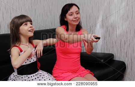 Mom And Daughter Watching A Humorous Show On Tv.