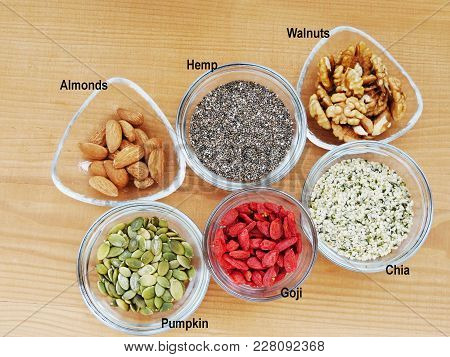 Five Superfood Seeds And Nuts Chia, Almond, Walnut, Hemp, Pumpkin In Glass Bowl Over Wooden Table