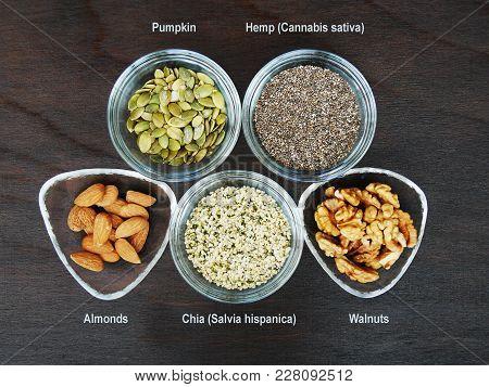 Five Superfood Seeds And Nuts Chia, Almond, Walnut, Hemp, Pumpkin In Glass Bowl Over Dark Wooden Tab