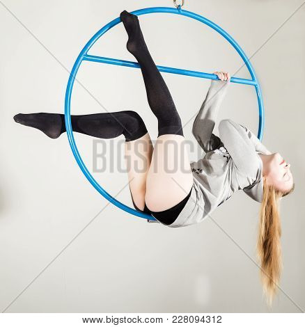 Aerial Acrobat On A Ring. A Young Woman Performs Acrobatic Elements On A White Background.
