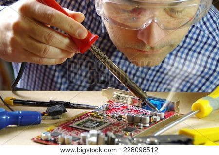 A Man At Work Using A Soldering Iron. Technician Focused On The Repair Of Electronic Equipment.