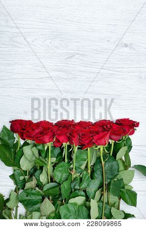 Bouquet Scarlet Roses On A Light Wooden Background. Close Up