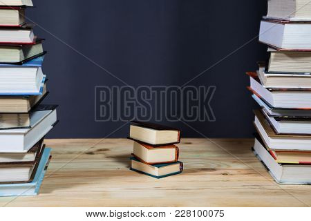 Pile Of Various Books On Bright Wooden Background. With Copy Space For Your Text