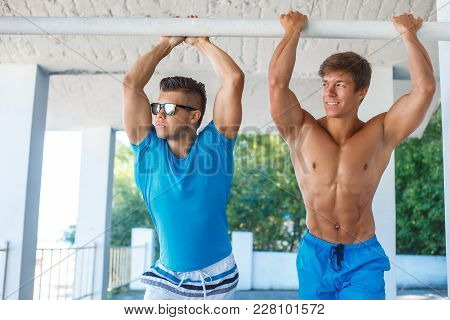 Muscular Guy In Sunglasses Standing With Hands Up.