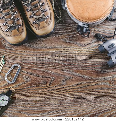 Hiking Or Travel Equipment With Boots, Compass, Binoculars, Matches And Travel Flask On Wooden Backg