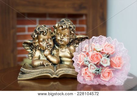 The Bouquet Of The Bride Lies On The Table Next To The Sculpture Of Two Little Angels Reading The Bo