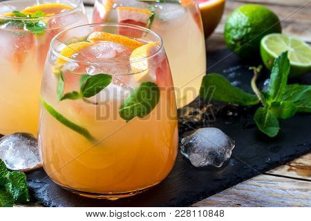 Grapefruit And Mint Gin Cocktail, Refreshing Drink With Ice On Wooden Background. Selective Focus