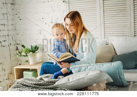 Cute Mother Reading A Book To Her Son At Home. Mom And Child Reading