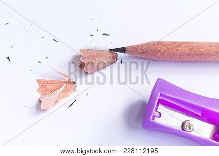 Violet Pencil-sharpener And Pencil Isolated On White Paper Background.  With Copy Space For Your Tex
