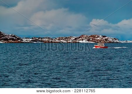 Motorboat With Red Bottom Moves Along The Sea Bay Against The Background Of Snow-capped Mountains