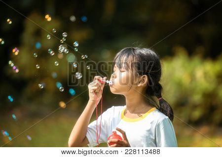 Children Are Happy To Play Blow Soap Bubbles In The Garden. Soft Focus Concept.