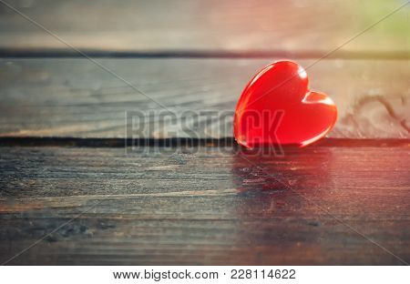 Plastic Red Heart On Wooden Background