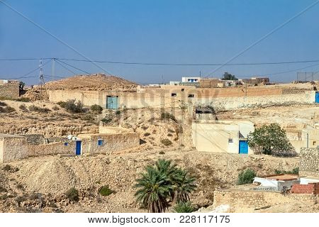 Arab Village In The Desert Of Tunisia Of Atlas Mountainswith Houses From The Sand And Blue Doors