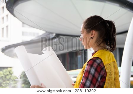Young Female Architect Holding Blueprint Plans And Reviewing Construction Plan