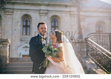 Wedding Day Groom Show Bride. Wedding Art. Beautiful Fairytale Newlywed Couple Hugging Near Old Medi