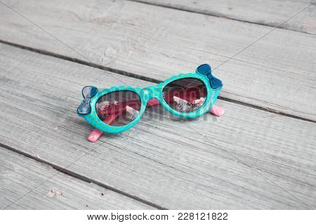 Beautiful Children's Blue Sunglasses On A White Wooden Background