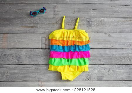 Beautiful Children's Bathing Suit ( Swimsuit)  And Sunglasses On A White Wooden Background
