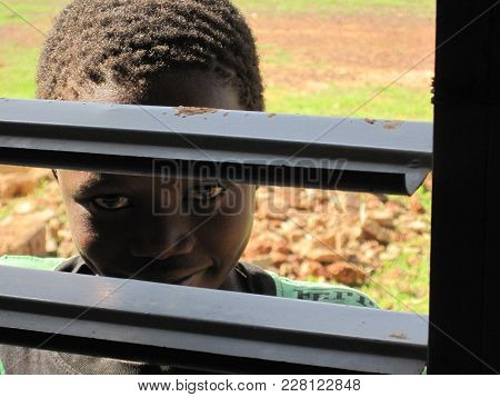 Gourcy, Nord Province Du Zondoma/ Burkina Faso  - 7/20/2009: Unidentified Child Looking In The Windo