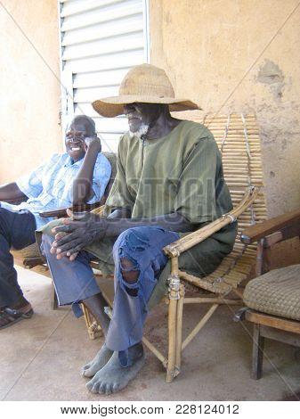 Gourcy/ Burkina Faso  - 7/20/2009: Unidentified Old Village Elder Sitting In Chair In Rural Village
