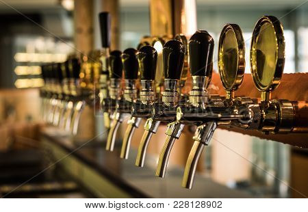 Row Of Draft Beer Tab On The Top Of Counter Bar In Closeup View, Time Of Celebration, Selective Focu
