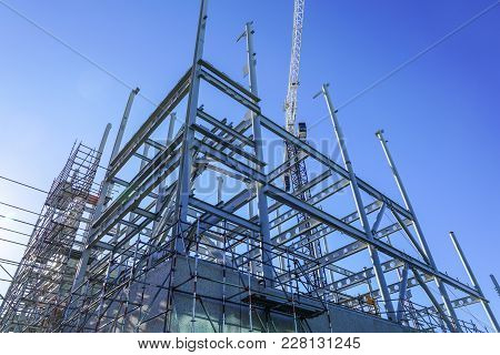 White Structural Steel Framework For New Building Against Deep Blue Sky.