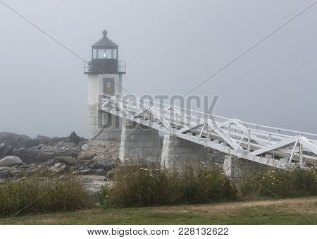 The Marshall Point Lighthouse Has Its Light On During A Very Foggy Summer Morning.