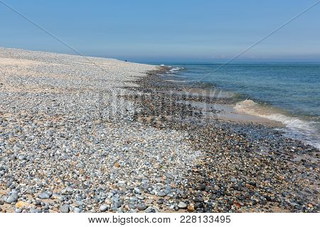Pebble Beach At German Island Dune Near Helgoland In Northsea With Bright Blue Sky